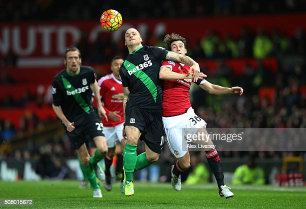Marko Arnautovic of Stoke City and Matteo Darmian of Manchester United compete for the ball during the Barclays Premier League match between...