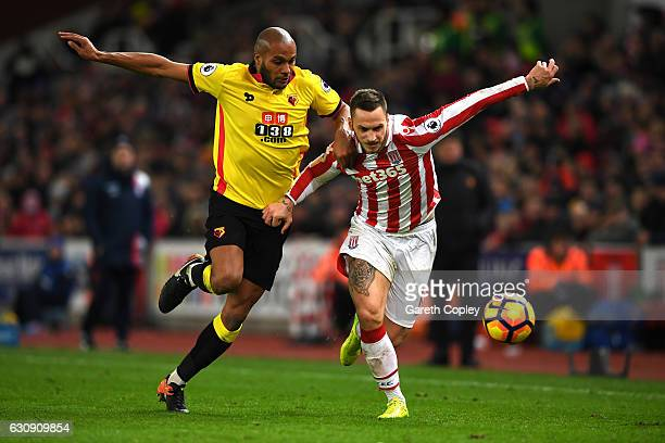 Marko Arnautovic of Stoke City and Younes Kaboul of Watford compete for the ball during the Premier League match between Stoke City and Watford at...