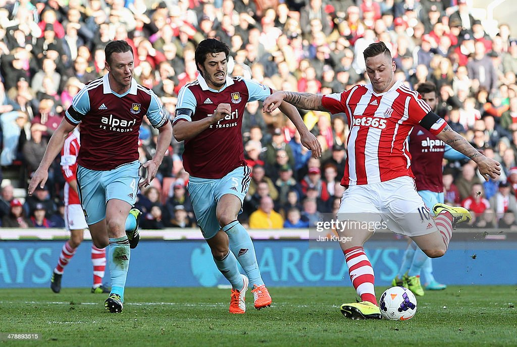 Marko Arnautovic of Stoke City beats Kevin Nolan (L), James Tomkins (2L) to score their second goal during the Barclays Premier League match between Stoke City and West Ham United at Britannia Stadium on March 15, 2014 in Stoke on Trent, England.