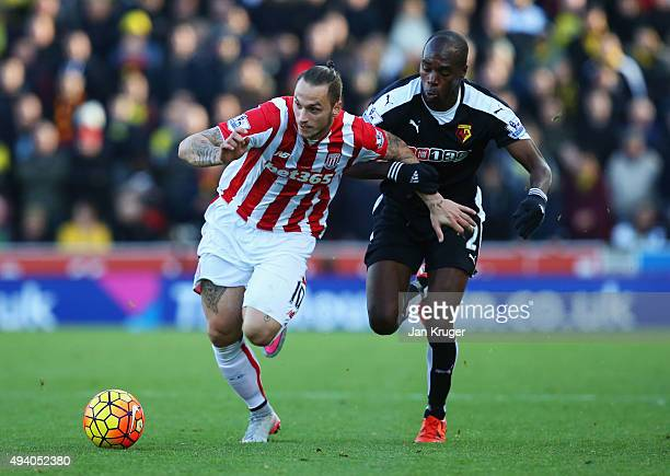 Marko Arnautovic of Stoke City is challenged by AllanRomeo Nyom of Watford during the Barclays Premier League match between Stoke City and Watford at...