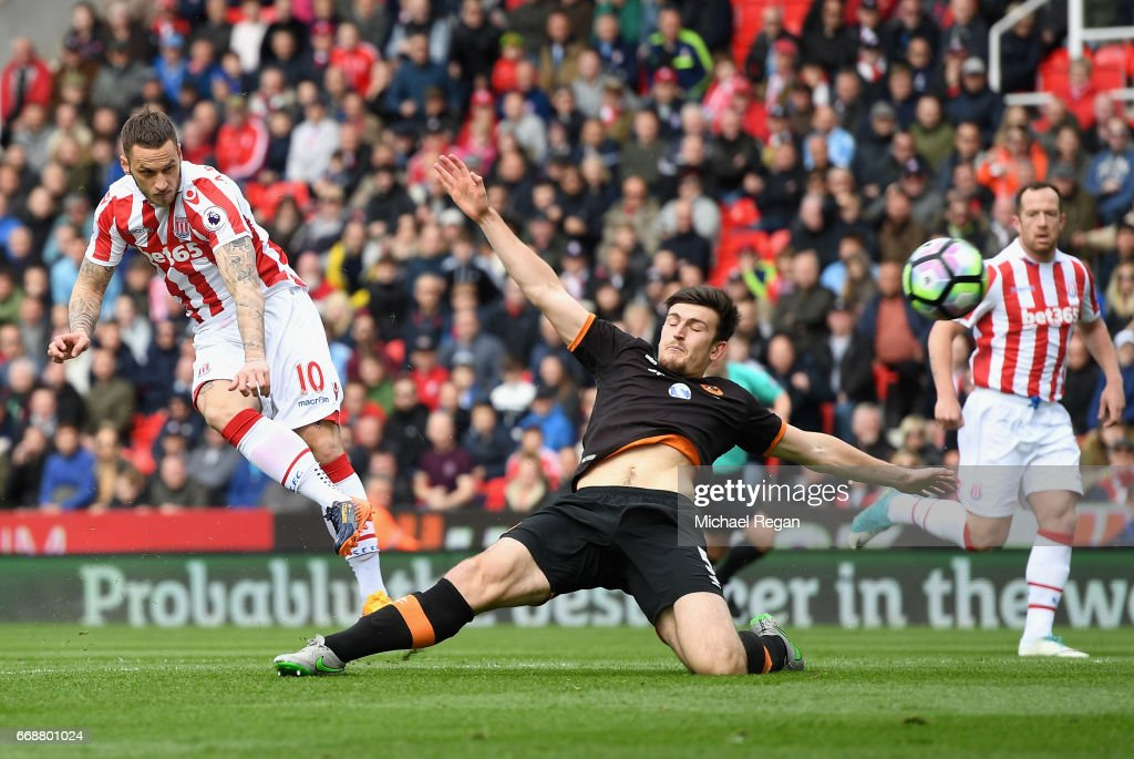 Marko Arnautovic of Stoke City (L) scores his sides first goal as Harry Maguire of Hull City attempts to block during the Premier League match between Stoke City and Hull City at Bet365 Stadium on April 15, 2017 in Stoke on Trent, England.