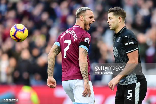 Marko Arnautovic of West Ham United celebrates after scoring his team's first goal as James Tarkowski of Burnley reacts during the Premier League...