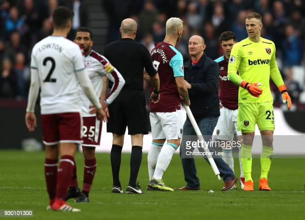 Marko Arnautovic of West Ham United confronts a pitch Invader who stole the corner flag during the Premier League match between West Ham United and...