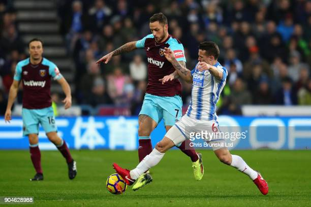 Marko Arnautovic of West Ham United is challenged by Jonathan Hogg of Huddersfield Town during the Premier League match between Huddersfield Town and...