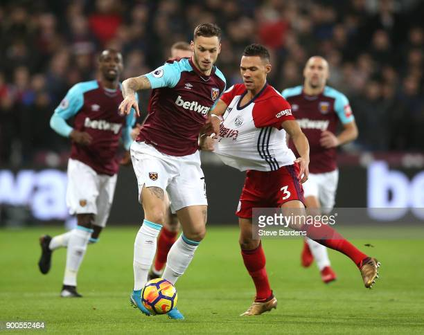 Marko Arnautovic of West Ham United is challenged by Kieran Gibbs of West Bromwich Albion during the Premier League match between West Ham United and...