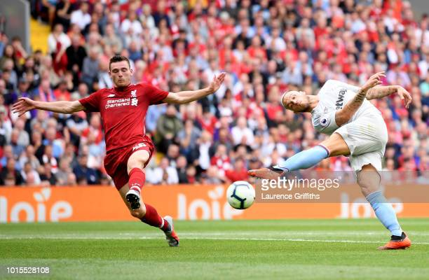 Marko Arnautovic of West Ham United misses a shot under pressure from Andy Robertson of Liverpool during the Premier League match between Liverpool...