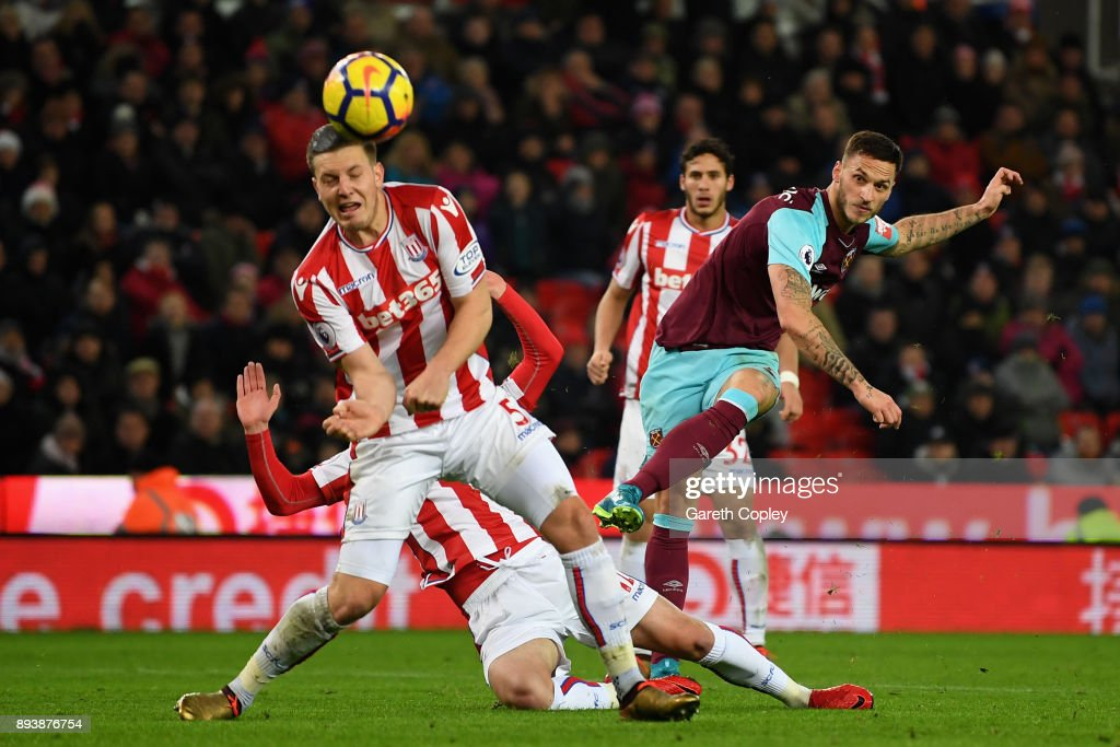 Marko Arnautovic of West Ham United shoots as Kevin Wimmer of Stoke City attempts to block during the Premier League match between Stoke City and West Ham United at Bet365 Stadium on December 16, 2017 in Stoke on Trent, England.