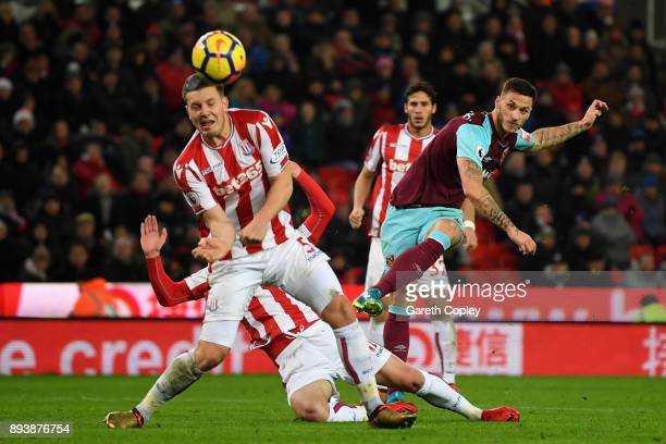 Marko Arnautovic of West Ham United shoots as Kevin Wimmer of Stoke City attempts to block during the Premier League match between Stoke City and...