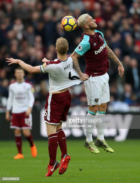 Marko Arnautovic of West Ham United wins a header over Ben Mee of Burnley during the Premier League match between West Ham United and Burnley at...