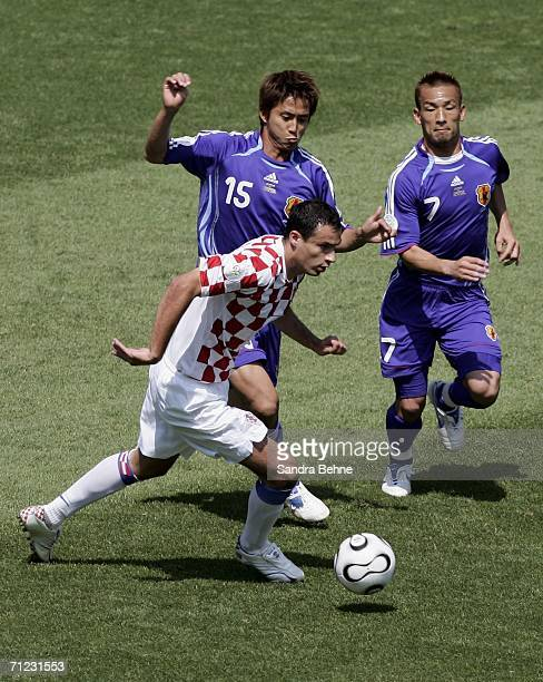 Marko Babic of Croatia is pursued by Takashi Fukunishi and Hidetoshi Nakata of Japan during the FIFA World Cup Germany 2006 Group F match between...