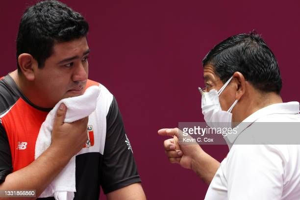 Marko Carrillo of Team Peru talks with his Father and Coach Marco Antonio Carrillo during the 25m Rapid Fire Pistol Men's Qualification on day ten of...