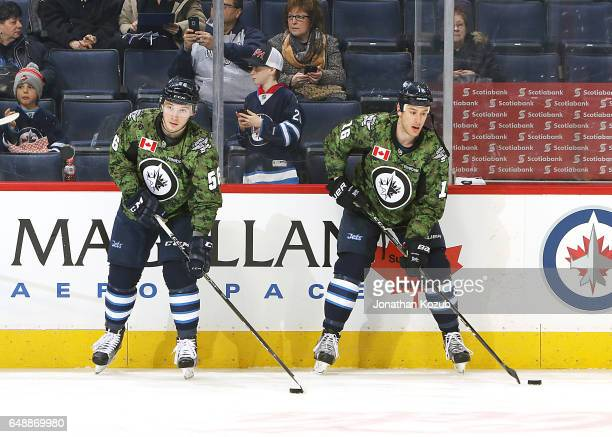 Marko Dano and Shawn Matthias of the Winnipeg Jets take part in the pregame warm up wearing a special military themed jersey for Canadian Armed...
