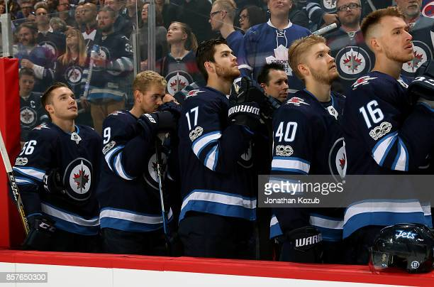 Marko Dano Andrew Copp Adam Lowry Joel Armia and Shawn Matthias of the Winnipeg Jets stand on the bench during the singing of 'O Canada' prior to...