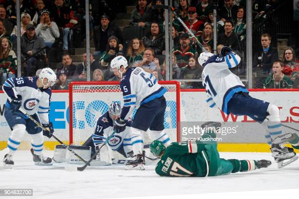 Marko Dano Connor Hellebuyck Dmitry Kulikov and Tyler Myers of the Winnipeg Jets defend against Marcus Foligno of the Minnesota Wild during the game...