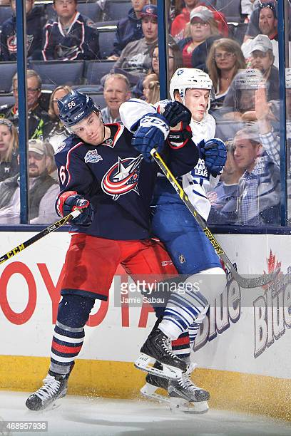 Marko Dano of the Columbus Blue Jackets checks Morgan Rielly of the Toronto Maple Leafs into the boards during the third period on April 8 2015 at...