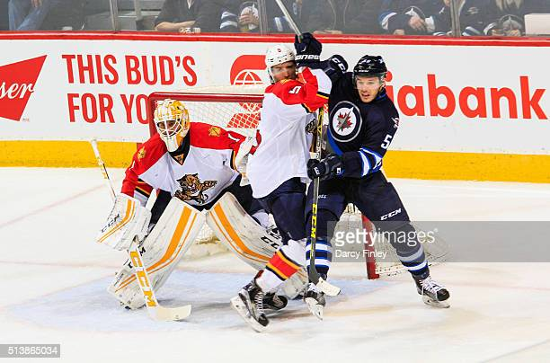 Marko Dano of the Winnipeg Jets and Aaron Ekblad of the Florida Panthers battle in front of goaltender Roberto Luongo during second period action at...