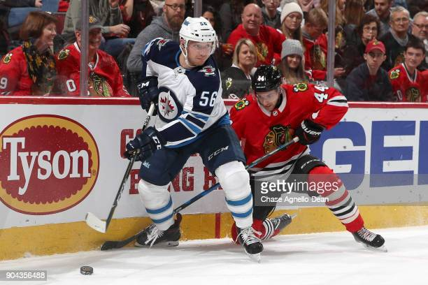 Marko Dano of the Winnipeg Jets and Jan Rutta of the Chicago Blackhawks battle for the puck in the first period at the United Center on January 12...