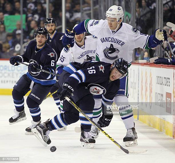 Marko Dano of the Winnipeg Jets and Nikita Tryamkin of the Vancouver Canucks battle for the puck in second period action in an NHL game at the MTS...