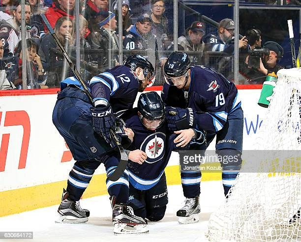 Marko Dano of the Winnipeg Jets gets helped off the ice by teammates Drew Stafford and Nic Petan after colliding heavily against the boards during...