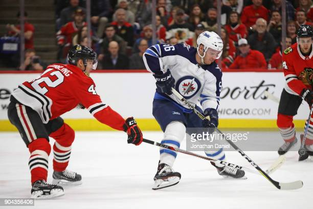 Marko Dano of the Winnipeg Jets gets off a shot under pressure from Gustav Forsling of the Chicago Blackhawks at the United Center on January 12 2018...