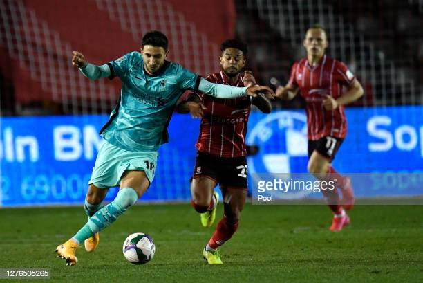 Marko Grujic of Liverpool battles for possession with Liam Bridcutt of Lincoln City during the Carabao Cup third round match between Lincoln City and...