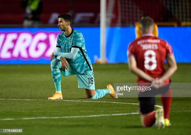 Marko Grujic of Liverpool takes a knee in support of the Black Lives Matter movement during the Carabao Cup third round match between Lincoln City...