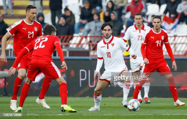 Marko Jankovic of Montenegro in action against Nemanja Matic and Mijat Gacinovic of Serbia during the UEFA Nations League C group four match between...