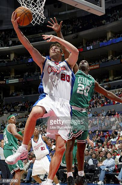 Marko Jaric of the Los Angeles Clippers tries to get a shot up under pressure from Gary Payton of the Boston Celtics in the first half on December 13...