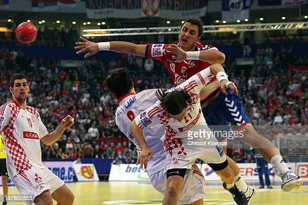 Marko Kopljar and Ivan Cupic of Croatia defend against Momir Ilic of Serbia during the Men's European Handball Championship second semi final match...