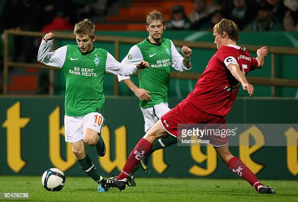 Marko Marin of Bremen and Martin Amedick of Kaiserslautern compete for the ball during the DFB Cup round of 16 match between between Werder Bremen...