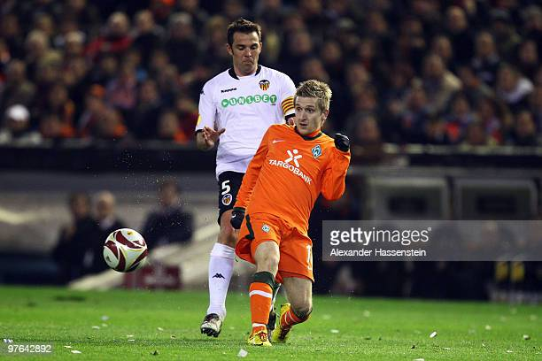 Marko Marin of Bremen battles for the ball with Carlos Marchena of Valencia during the UEFA Europa League round of 16 first leg match between...