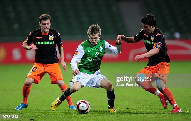 Marko Marin of Bremen is challenged by Juan Mata and Carlos Marchena of Valencia during the UEFA Europa League round of 16 second leg match between...