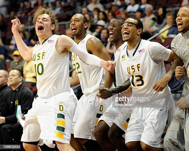 Marko Petrovic, Perris Blackwell, Moustapha Diarra and Rashad Green of the San Francisco Dons celebrate on the bench late in their 76-59 victory over...