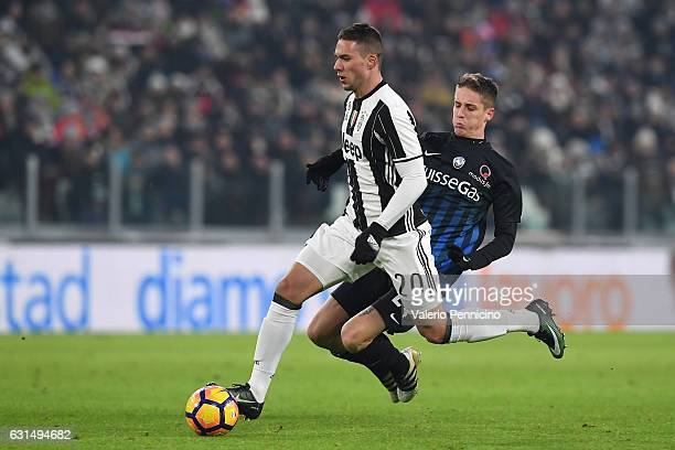 Marko Pjaca of FC Juventus is challenged by Andrea Conti of Atalanta BC during the TIM Cup match between FC Juventus and Atalanta BC at Juventus...