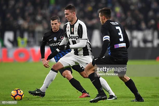 Marko Pjaca of FC Juventus is challenged by Remo Freuler and Rafael Toloi of Atalanta BC during the TIM Cup match between FC Juventus and Atalanta BC...