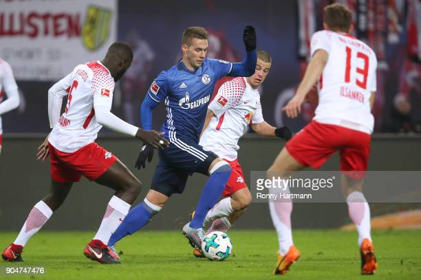Marko Pjaca of Schalke is attacked by Dayot Upamecano Diego Demme and Stefan Ilsanker of Leipzig during the Bundesliga match between RB Leipzig and...