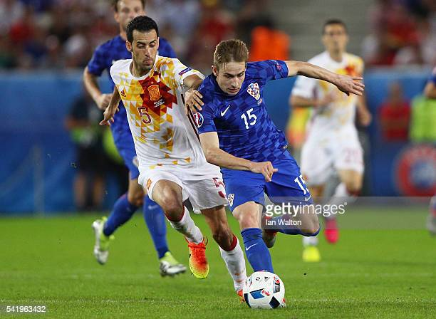 Marko Rog of Croatia and Sergio Busquets of Spain compete for the ball during the UEFA EURO 2016 Group D match between Croatia and Spain at Stade...