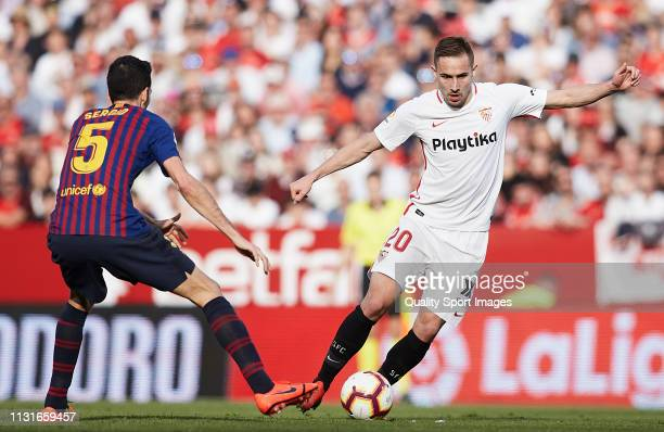 Marko Rog of Sevilla FC competes for the ball with Sergio Busquets of FC Barcelona during the La Liga match between Sevilla FC and FC Barcelona at...