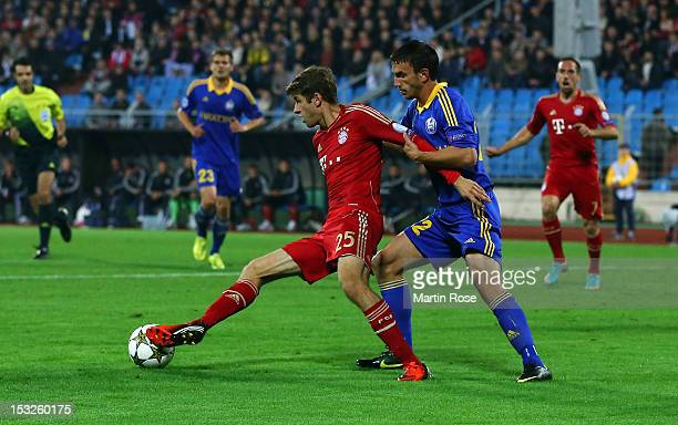 Marko Simic of Borisov and Thomas Mueller of Muenchen battle for the ball the during UEFA Champions League group F match between FC Bayern Muenchen...