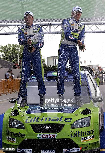 Winners of the WRC Acropolis Rally Marcus Gronholm and Timo Rautiainen of Finland spray champagne while standing on their Ford Focus RS WRC at the...