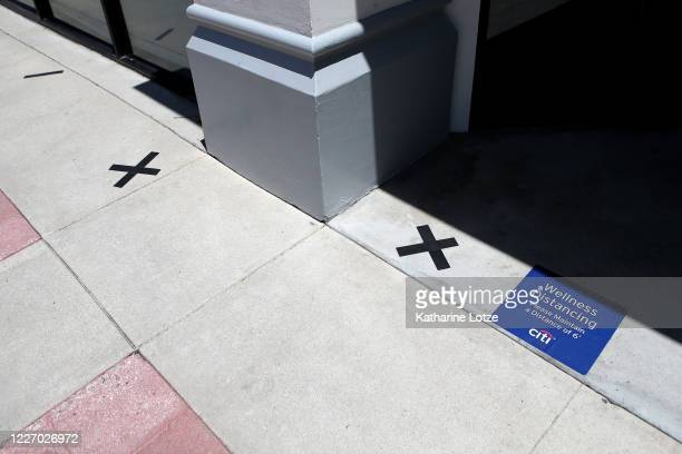 Marks on the sidewalk encouraging social distancing are left outside a bank on May 25 2020 in Westwood California Government guidelines encourage...