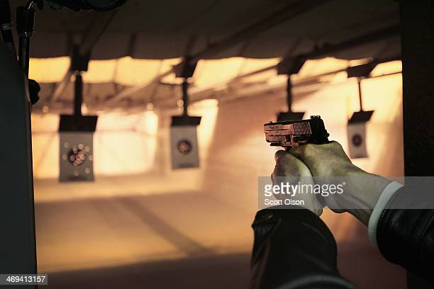 A marksman sights in on a target during a class he was taking to qualify for an Illinois concealed carry permit on February 14 2014 in Posen Illinois...