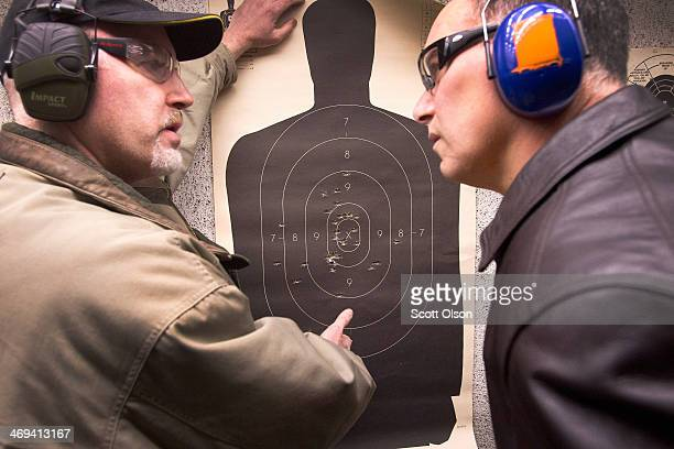 Marksmanship instructor Craig Marshall scores Hector Torres' target after he fired his pistol to qualify for an Illinois concealed carry permit on...