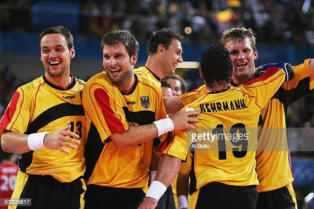 Markus Baur Daniel Stephan and Florian Kehrmann celebrate Germanys win over Russia in the men's handball Semi Finals on August 27 2004 during the...