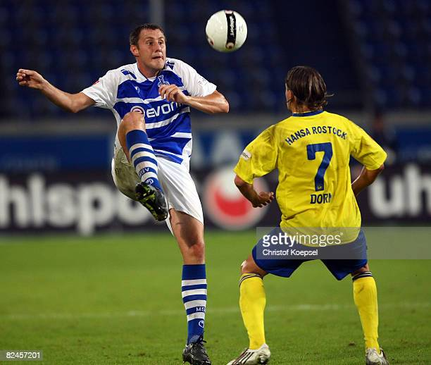 Markus Brzenska of Duisburg plays the ball over Regis Dorn of Rostock during the 2nd Bundesliga match between MSV Duisburg and Hansa Rostock at the...
