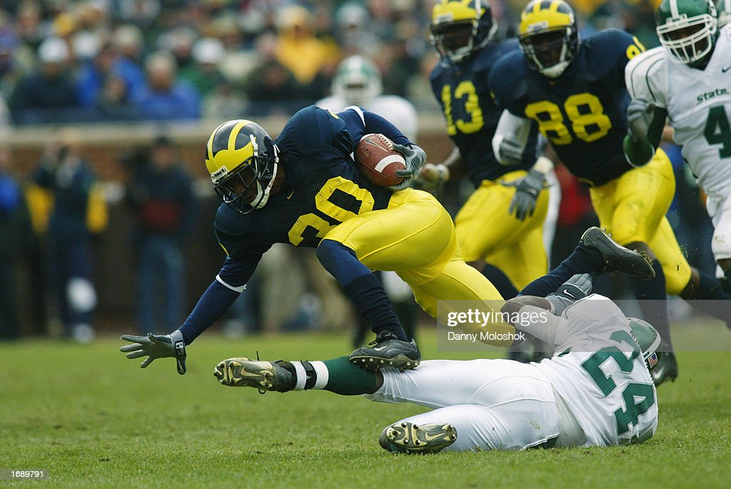 Markus Curry #30 of the Michigan Wolverines is taken down by Jeremiah McLaurin #24 of the Michigan State Spartans during the game on November 2, 2002 at Michigan Stadium in Ann Arbor, Michigan. Michigan won 49-3.