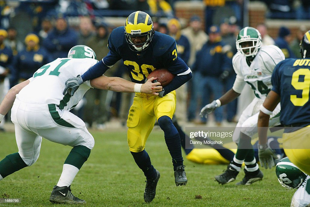 Markus Curry #30 of the Michigan Wolverines tries to hold off a tackle by Chris Morris #51 of the Michigan State Spartans during the game on November 2, 2002 at Michigan Stadium in Ann Arbor, Michigan. Michigan won 49-3.