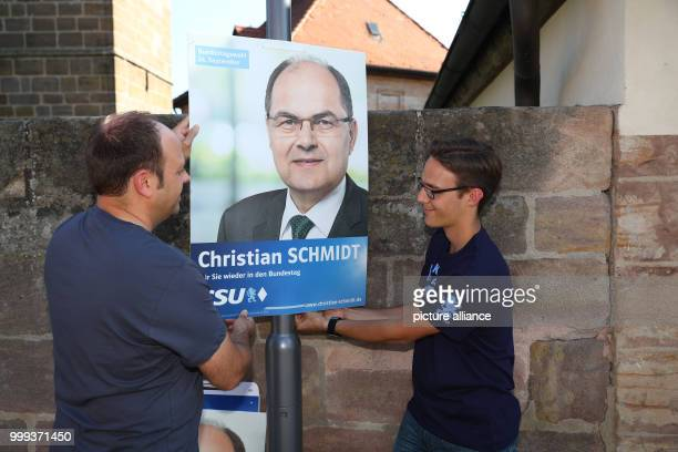 Markus Diessl Zeugendorf municipal councilor and Andre Kraus Seukendorf municipal councilor putting up an electoral campaign poster of the CSU in...
