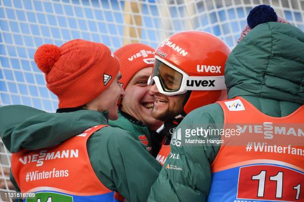 Markus Eisenbichler of Germany celebrates with teammates Karl Geiger Richard Freitag and Stephan Leyhe following their victory in the Men's Team Ski...
