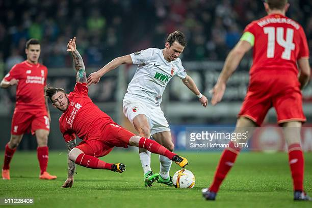 Markus Feulner of Augsburg is challenged by Alberto Moreno of Liverpool during the UEFA Europa League Round of 32 first leg match between FC Augsburg...